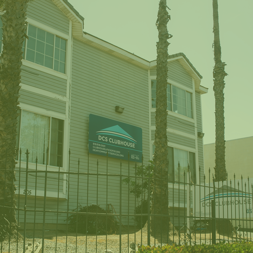 Background: victoria house style with a big blue sign of DCS Clubhouse logo and information mounted on the building on the left, another big white sign of DCS logo and information installed in the ground on the right; foreground: 3 palm trees along with the iron fence and bushes; text: DCS Clubhouse (the location is in National City, CA, in South San Diego County); Address 205 National City Blvd., National City, CA 91950; Email clubhouse@dcsofsd.org; Phone VP 619 618 0501