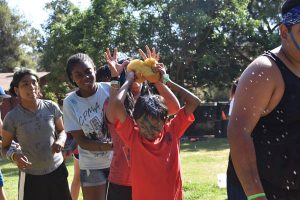 outdoor activity: campers line-up and passing the soaked sponge above the head