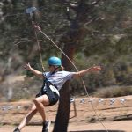 outdoor; a camper with light blue helmet rides on the zipline