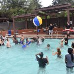 outdoor swimming pool; campers and counselors playing beach volleyball in the water