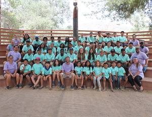 Background: outdoor theater audience seating; group of young campers and counselors smiling at the camera