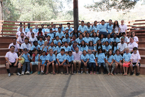 outdoor theater audience; a large group of campers in blue t-shirts and counselors in pink t-shirts seating and smiling at the camera
