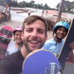 Man with a short beard, looking at the camera and smiling. Holding up part of a purple skateboard. Behind him, two children wearing helmets, looking at the camera and smiling, also holding up skateboards.