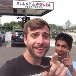 two people looking and pointing at camera, semi-smiling. Behind them are some cars and a sign that says Plant Power Fast Food.