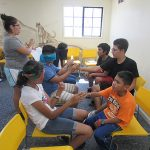 Indoor workshop setting; far left: counselor; left: 3 campers with blindfolded and they reach their hands out to their opponents' hands signing for these blindfolded campers figure out what their opponents are saying