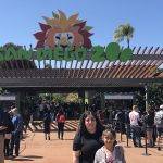 outdoor, San Diego Zoo with a lot of people; foreground: adult on the left with long black hair and black shirt; a child on the right with black pulled back hair, light purple jacket cover pink shirt with printed of smiling watermelon with eyeglasses; both looking at the camera