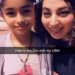 Background: outdoor with a tree in the top right corner; foreground: a young child on the left with black pulled back hair, light purple jacket cover pink shirt with printed of smiling watermelon with eyeglasses; adult on the right with long black hair and black shirt; both smiling at the camera; black box across the image with white text: Date to the Zoo with my Little!