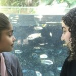 Background: indoor, aquarium; foreground: adult on the left with long black hair and black t-shirt; child on the right-pointing the display images with information with light purple jacket cover pink shirt; both looking at the fish