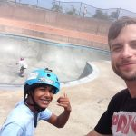"""Man in black shirt on the right, short beard, looking at the camera squinting and smiling. On the left, a young man in light blue shirt, with blue helmet, looking at the camera, smiling, gesturing the """"hang loose"""" sign. Behind them, a skate park."""