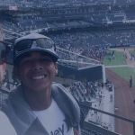 Background: baseball game; foreground: adult on the left with brown hair, sunglasses, and white t-shirt; child on the right with sunglasses on the cap and white t-shirt smiling at the camera