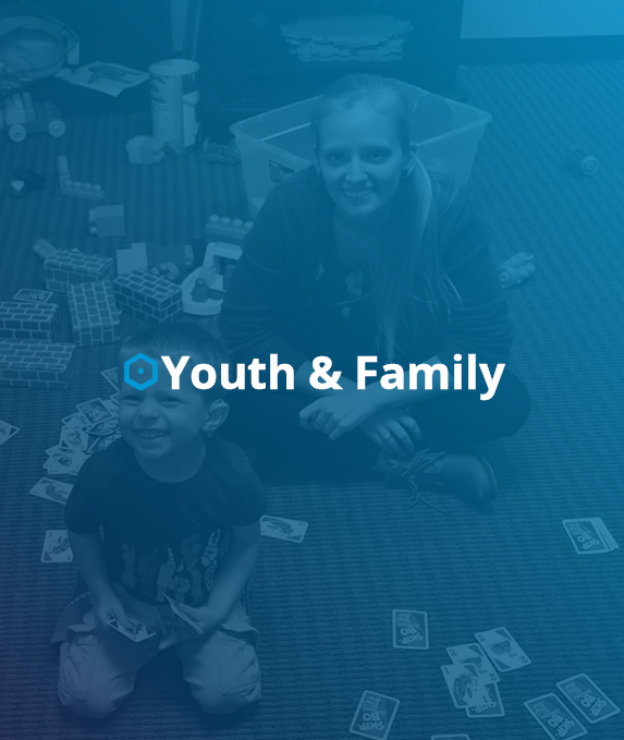 toys and playing cards laying on the floor, both young child and adult sitting on the floor smiling at the camera