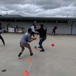 outdoor background; several students playing dodgeball activity