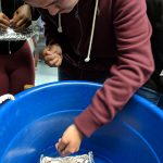 a young man with dark red sweater drop some coins in a foil boat in the blue tub