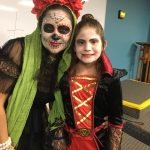 Background is a whiteboard and blue wall. A woman in calavera skull makeup poses next to a young girl in a vampire costume.