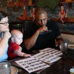 """Background is an Asian mural. Two adults and a baby sits at the table. They are looking at pictures of different signs for food. The woman in blue shirt is signing """"cereal"""" and the man in black shirt is signing """"kiss-fist"""". The baby in the red shirt is reaching towards some paper."""