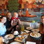 Background is an Asian mural. Three adults and baby sits at a table with food and plates. They are all looking at the camera and smiling except for the baby who is eyeing a plate of salad.
